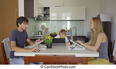 A young woman and man are working in their living room with the kitchen in the background. Their son is studying online using a tablet. They both have to work remotely due to the Covid-19 restrictions. Covid-19 pandemics concept.