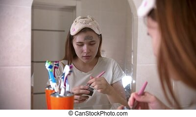 A young woman applying a face mask on her face using a brush