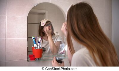 A young woman applying a grey face mask on her face using a brush