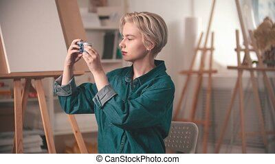 A young woman artist looking at two tubes of a blue paint