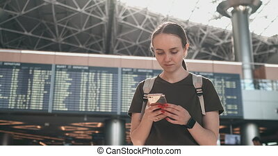 A young woman at the airport with a smartphone near the...