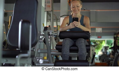 A young woman at the gym doing exercises holding a phone in front of her eyes in her hands. All the attention is in the phone. The concept of dependence on social networks. Mobile addiction concept