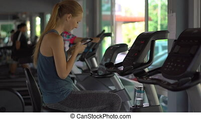 A young woman at the gym on an exercise bike holding the...