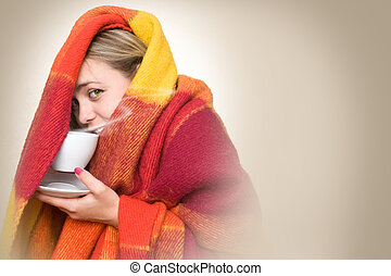 hot drink from a cup. - A young woman caught a cold, wrapped...
