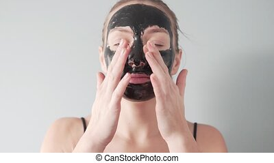 A young woman checks a black mask on her face