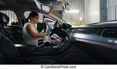 A young woman cleansing steering wheel of car. Mid shot