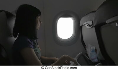 A young woman closes the porthole during an air travel on an airplane. The concept of tourism