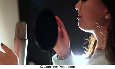 A young woman comes to the mic and start singing in...