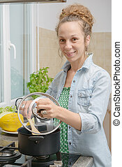 young woman cooking dinner in the kitchen