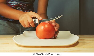 A young woman cuts in half a fresh juicy tomato with knife on the cutting board in the kitchen interior.