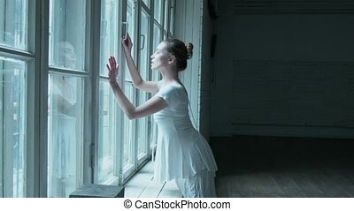 A young woman dances near a window in a white dress and pantyhose in a mesh. Beautiful blonde near the old big window makes a dance movement.