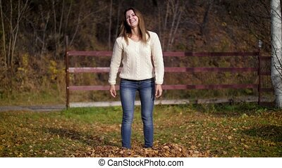 A young woman dancing in a pile of fallen dry autumn leaves. Autumn fun. Girl enjoys autumn. 4k 60fps slow motion.