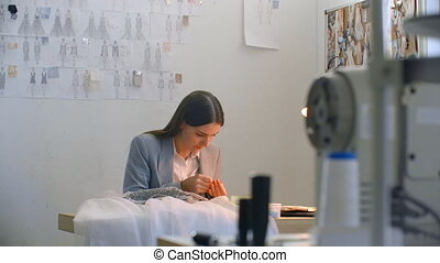 A young woman designer making a dress in the Studio dress. Tailoring Studio sewing beads and jewelry. Seamstress decorates a dress in the Studio