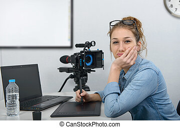young woman designer using graphics tablet for video editing...