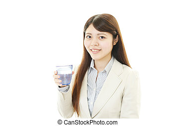A young woman drinking a glass of w