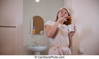 A young woman drinking coffee standing in the bathroom doorway at the morning