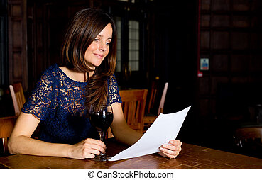 a young woman drinking wine and reading letter