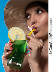 A young woman drinks a drink on a hot summer day and has a hat on her head.