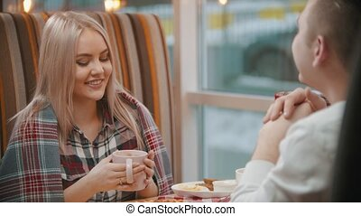A young woman drinks coffee and talking with her boyfriend in cafe