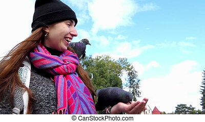 A young woman feeds doves from her hands in slo-mo