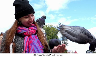 A young woman feeds pigeons from her hands in slo-mo