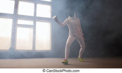 A young woman fencer in white protective costume performing ...
