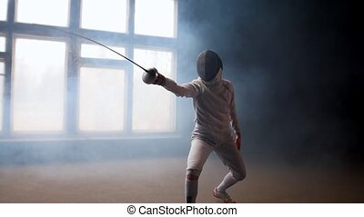 A young woman fencer showing basic attack movements on the ...