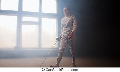 A young woman fencer walking to the fighting area with loose...