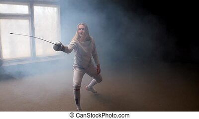 A young woman fencer with loose hair in white costume ...