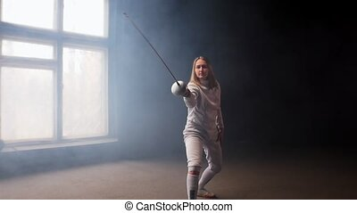A young woman fencer with loose hair in white protective ...