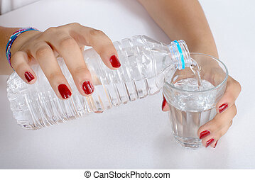 a young woman filled a glass of water with plastic bottle