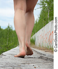 A young woman goes barefoot on the stone parapet