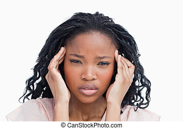 A head shot of a young woman who is having a migraine