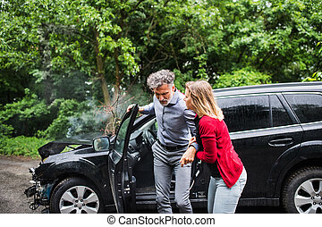 A young woman helping a man to get out of the car after a car accident.