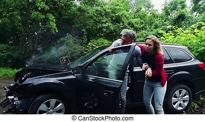 A young woman helping a man to get out of the crashed car...
