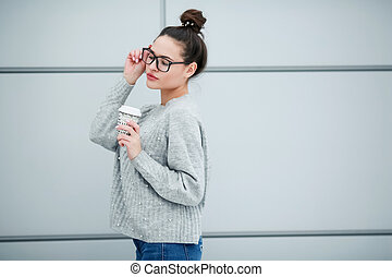 A young woman holding a Cup of coffee in her hands on the street on a monochrome background