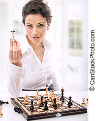 a young woman holding chess pieces - a young woman holding...
