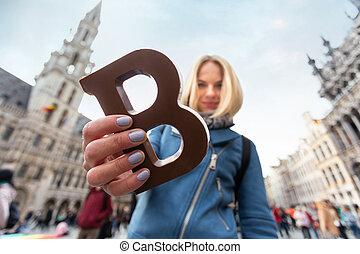 A young woman holds a bar of Belgian chocolate in the shape of the letter B in her hands.