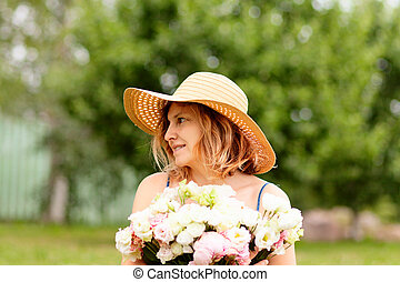 A young woman holds a large bouquet of peonies. In a straw hat with wide brim. Looks to the right.