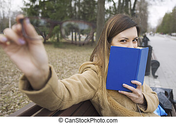 A young woman holds glasses in hand and book - sitting on the bench at park