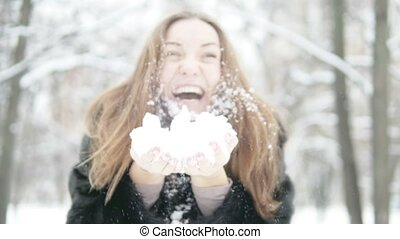 A young woman holds snow in her hands.