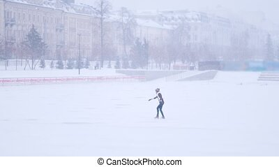 A young woman ice skating on the open rink outside alone....