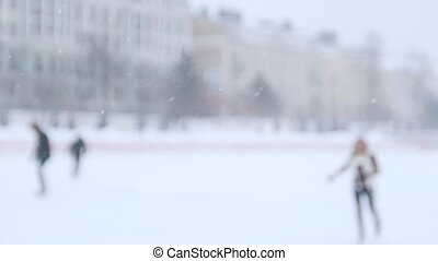 A young woman ice skating outside and skate closer to the...