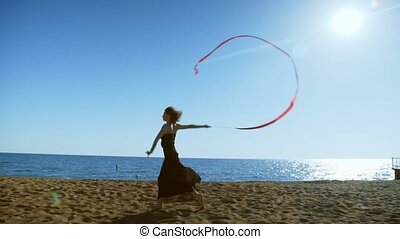 A young woman in a black dress is running on the sand and doing a drawing of a red ginastic ribbon