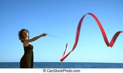 A young woman in a black dress is standing on the sand and doing a drawing of a red ginastic ribbon