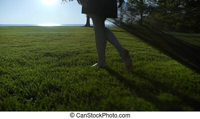 A young woman in a black dress with a black cloth walks on the green grass