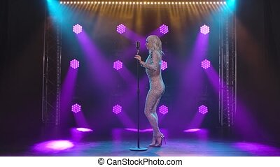 A young woman in a chic tight-fitting jumpsuit in rhinestones and a shiny headdress dances near a vintage microphone on stage. Slow motion