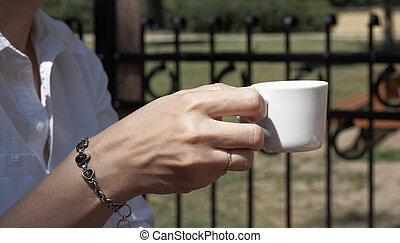 A young woman in a garden restaurant holds a coffee in hand, with trees in the background
