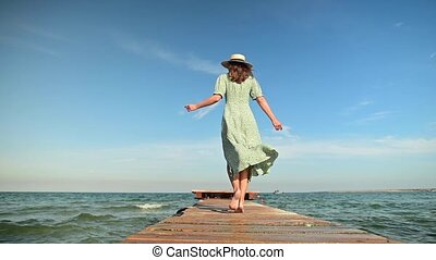 A young woman in a green summer dress and a straw hat in slow motion walks along a wooden pier in the morning on the sea during the wind. Walk grace beauty and femininity.