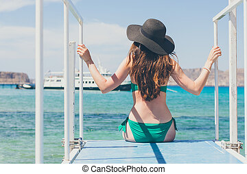 A young woman in a green swimsuit and a black hat sits on a pier and looks at the ships. Rear view